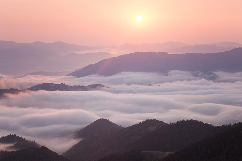 Sunrise over cloudy mountain ridge